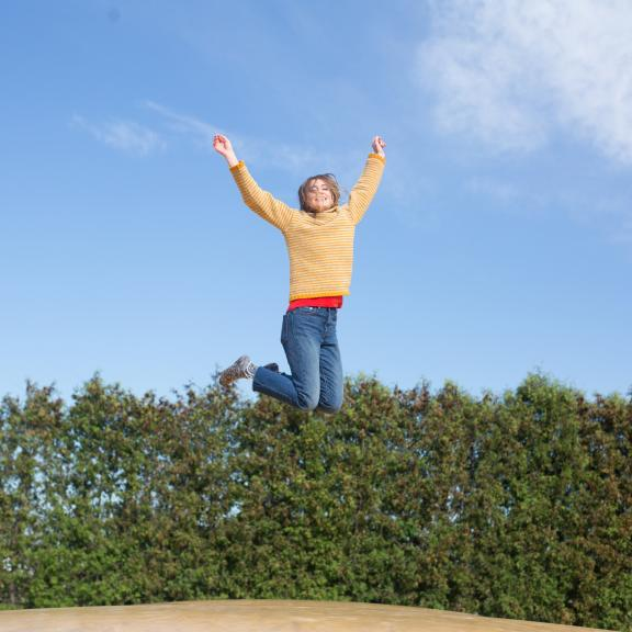 happy woman jumping on field