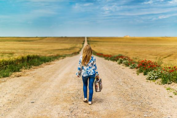 woman walking on an empty countryside road