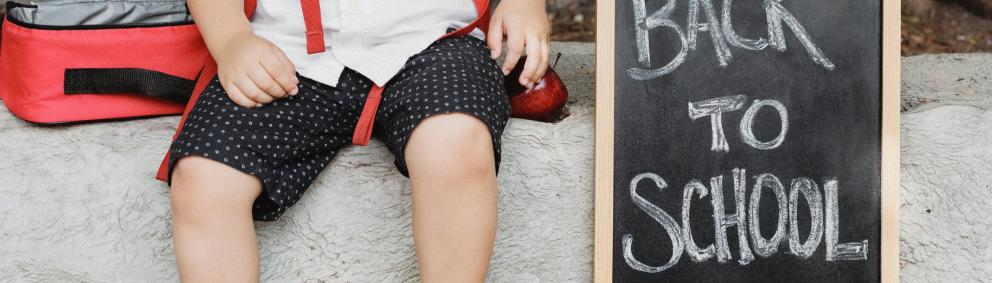 child sat on a bench with a back to school chalk board sign